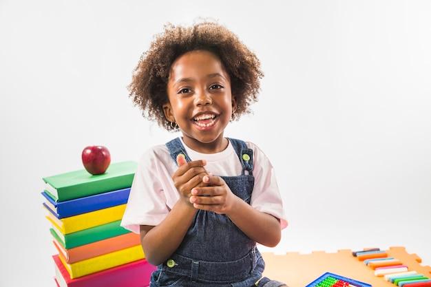Jong geitjezitting met boeken en het glimlachen in studio Gratis Foto