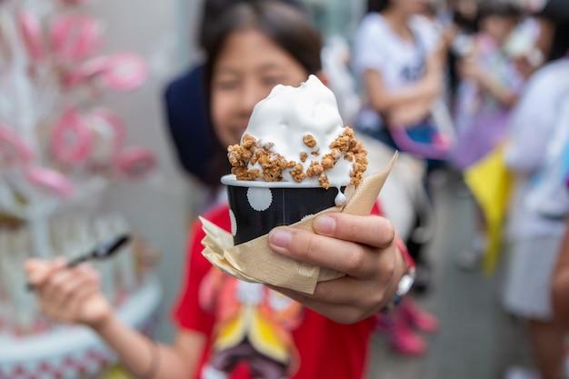 Jong gelukkig aziatisch meisje dat van haar zachte room, japans roomijs, met granolabovenste laagje geniet Premium Foto