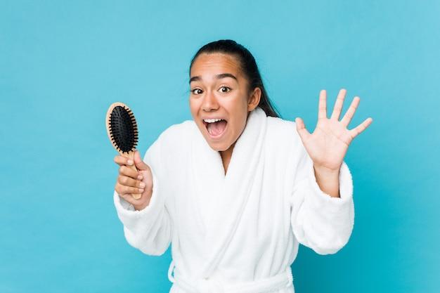 Jong gemengd ras indiër die een haarborstel houdt die een overwinning of een succes viert Premium Foto