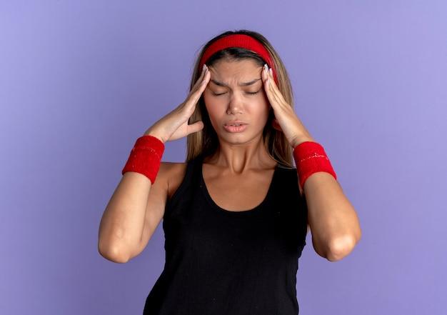 Jong geschiktheidsmeisje in zwarte sportkleding en rode hoofdband die onwel haar hoofd aanraken met handen die aan sterke hoofdpijn lijden die zich over blauwe muur bevinden Gratis Foto