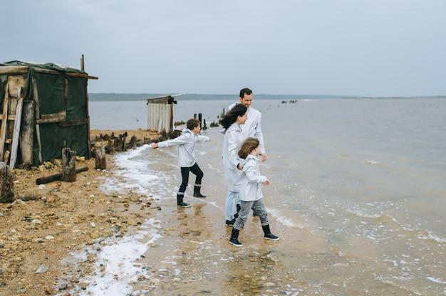 Jong gezin heeft plezier in de buurt van de barakken op het meer Premium Foto