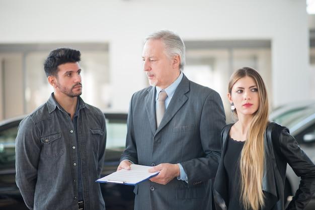 Jong gezin in gesprek met de verkoper en het kiezen van hun nieuwe auto in een showroom Premium Foto