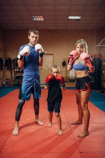 Jong gezin in handschoenen op kickbokstraining, sportschool interieur. paar en kleine jongen op zelfverdedigingstraining, martial arts oefenen Premium Foto