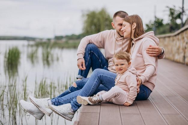 Jong gezin met hun kleine baby kind in park aan het meer Gratis Foto