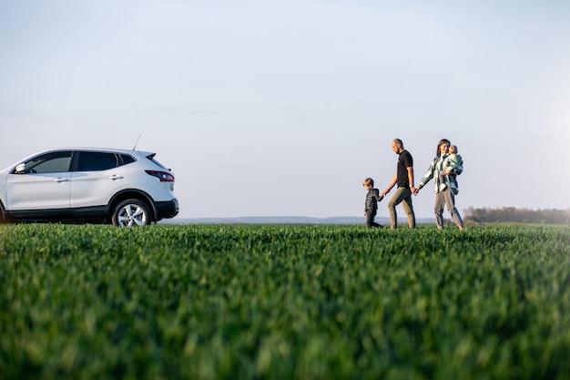 Jong gezin met kinderen die met de auto reizen, stopte in het veld Gratis Foto