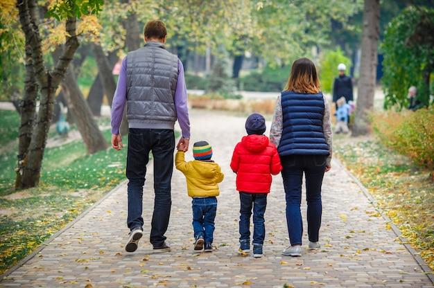Jong gezin met kinderen wandelingen in het park Premium Foto