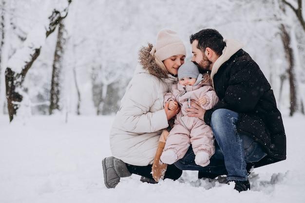 Jong gezin met kleine dochter in een winter bos vol met sneeuw Gratis Foto