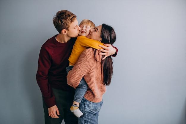Jong gezin met zoontje samen op grijs Gratis Foto