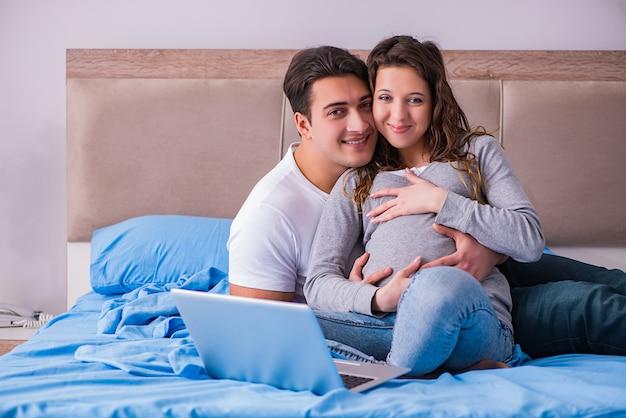 Jong gezin met zwangere vrouw die baby in bed verwacht Premium Foto