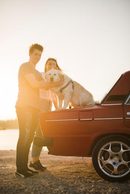 Jong gezin op een road trip met hun hond Gratis Foto