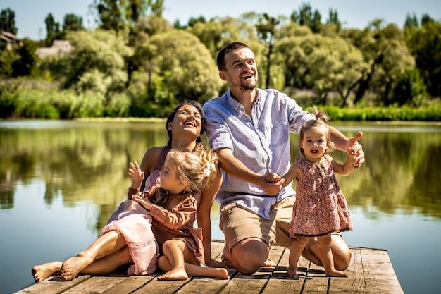 Jong gezin op pier in de buurt van het meer Gratis Foto