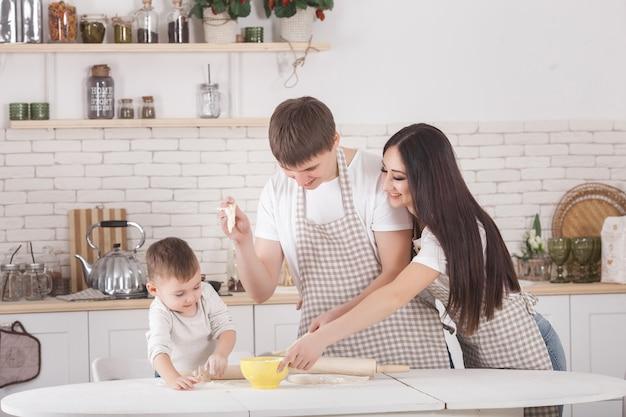Jong gezin samen koken. man, vrouw en hun kleine baby op de keuken. familie die het deeg met bloem kneedt. mensen koken het diner of ontbijt. Premium Foto