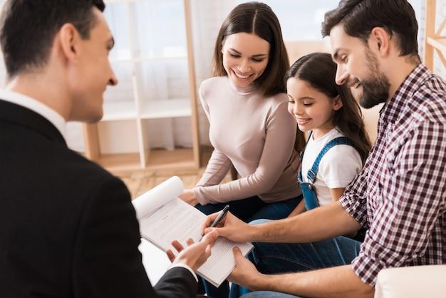 Jong gezin tekent associatieovereenkomst om huis te kopen Premium Foto