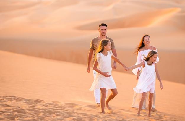 Jong gezin van vier in grote zandwoestijn Premium Foto