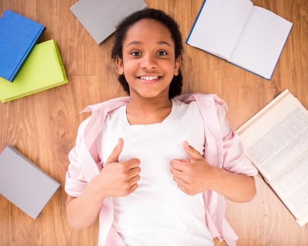 Jong glimlachend mulatschoolmeisje dat op de vloer legt. Premium Foto