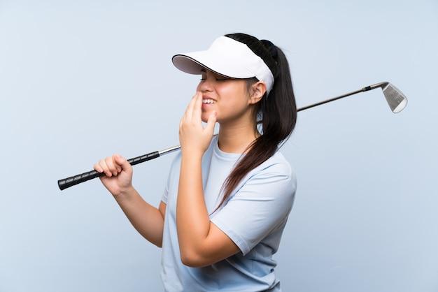 Jong golfspeler aziatisch meisje over geïsoleerde blauwe muur die veel glimlacht Premium Foto