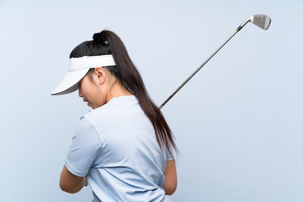 Jong golfspeler aziatisch meisje over geïsoleerde blauwe muur Premium Foto