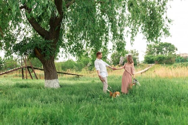 Jong houdend van paar dat pret heeft en op het groene gras op het gazon loopt met hun geliefde binnenlandse hondenras beagle en een boeket van wilde bloemen Premium Foto