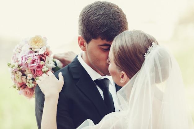 Jong huwelijkspaar die van romantische ogenblikken genieten in openlucht dicht omhoog Premium Foto