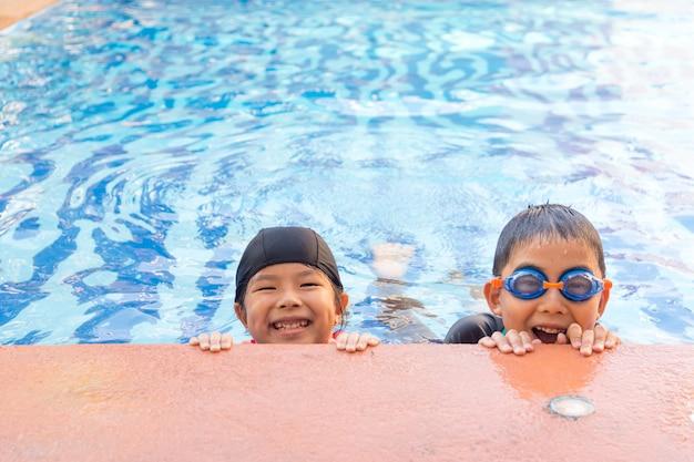 Jong jongen en meisje die in pool zwemmen. Premium Foto
