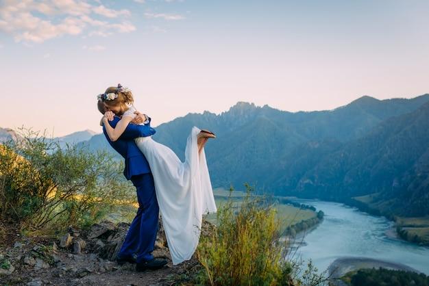 Jong jonggehuwdepaar die op perfecte mening van bergen en blauwe hemel koesteren Premium Foto