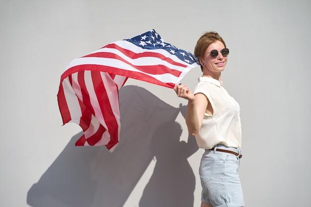 Jong kaukasisch glimlachend meisje die in zonnebril de vlag van de vs erachter houden als een mantel die door wind wordt gegolfd Premium Foto