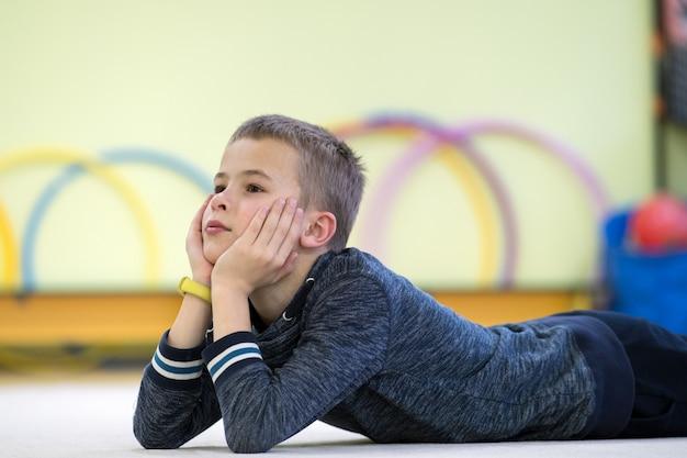Jong kindjongen het bepalen en relaxiong terwijl het rusten op de vloer binnen sportenruimte in een school na opleiding. Premium Foto