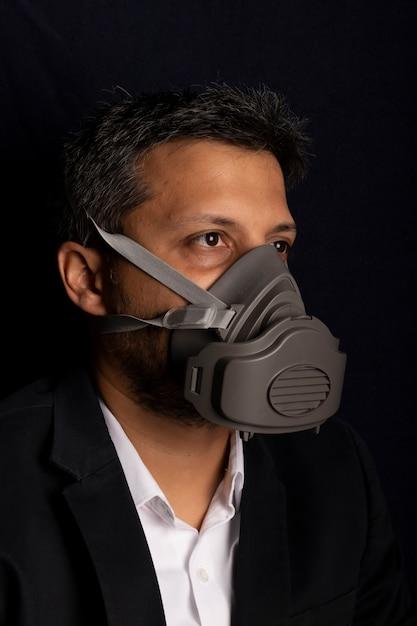 Jong knap met industrieel masker om de verspreiding van besmettelijke virussen of chemische gassen te voorkomen Premium Foto