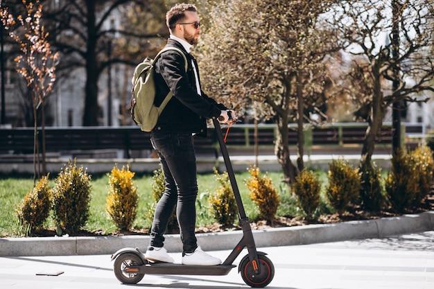 Jong knap personenvervoer op autoped in het park Gratis Foto