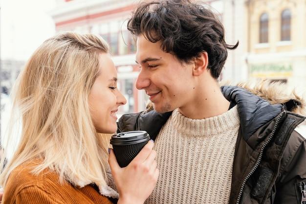 Jong koppel buiten genieten van kopje koffie Gratis Foto