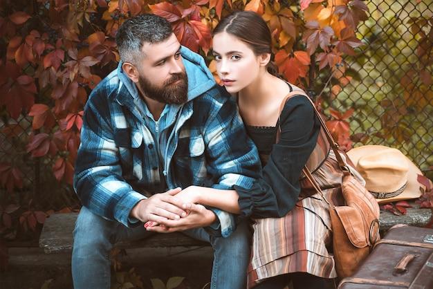 Jong koppel buiten zitten in de herfst park. Premium Foto