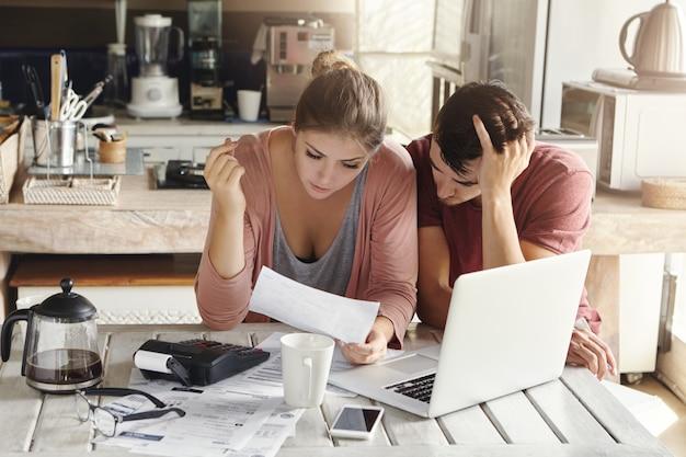 Jong koppel doen papierwerk in de keuken: gefrustreerd vrouw leest document samen met haar man die zijn hoofd in wanhoop houdt, zittend aan tafel met laptop Gratis Foto