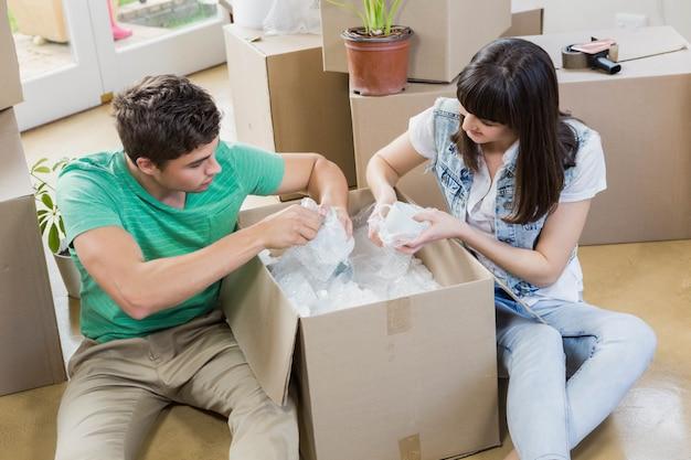 Jong koppel elkaar bijstaan tijdens het uitpakken van kartonnen dozen in een nieuw huis Premium Foto
