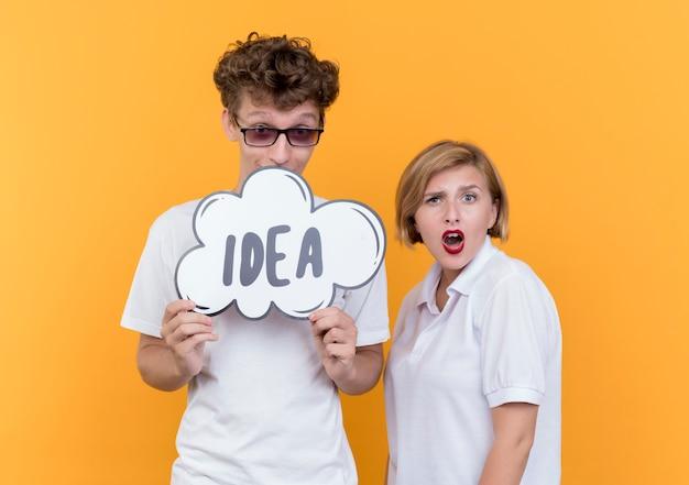 Jong koppel gelukkig man met tekstballon bord met woord idee terwijl zijn vriendin verward staande over oranje muur Gratis Foto