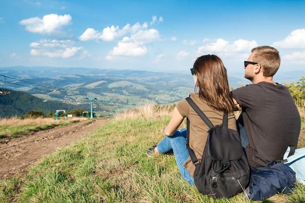 Jong koppel genieten van bergen landschap, zittend op de heuvel Gratis Foto