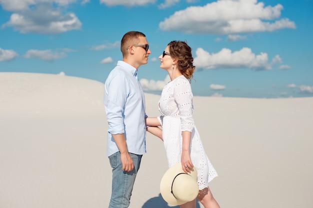 Jong koppel genieten van de zonsondergang in de duinen. romantische reiziger wandelingen in de woestijn. avontuurlijke reizen levensstijl concept Premium Foto