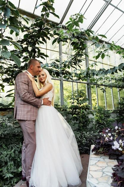Jong koppel genieten van romantische momenten tijdens een wandeling in het park. stijlvolle bruid en bruidegom poseren en zoenen in het park op hun trouwdag. elegante bruid in mooie witte jurk, bruidegom in een pak. Premium Foto