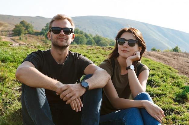 Jong koppel glimlachen, genieten van bergen lanscape, zittend op de heuvel Gratis Foto