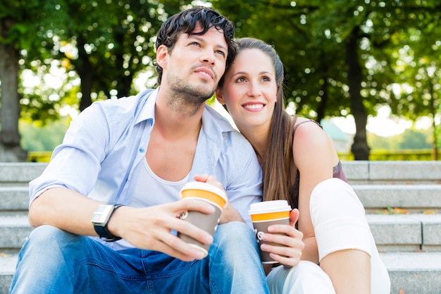 Jong koppel in stadspark koffie drinken Premium Foto