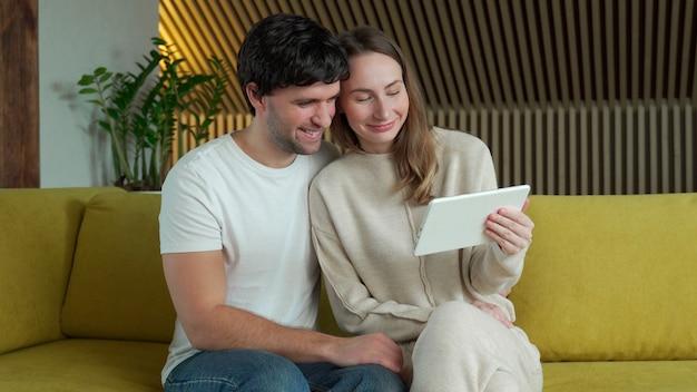 Jong koppel kijken naar media-inhoud online in een tablet zittend op een bank thuis Premium Foto