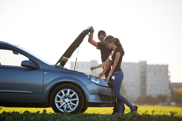 Jong koppel, knappe man en aantrekkelijke vrouw bij auto met gepofte kap oliepeil in motor controleren met peilstok op heldere hemel. transport, voertuigproblemen en storingen concept. Premium Foto