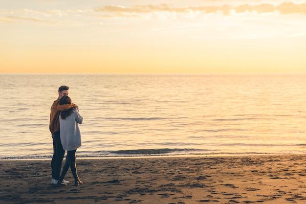 Jong koppel knuffelen op zee kust in avond Gratis Foto
