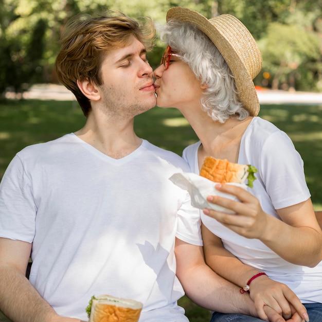 Jong koppel kussen en genieten van hamburgers in het park Gratis Foto