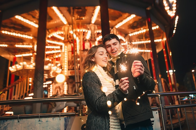 Jong koppel kussen en knuffelen buiten in nacht straat in de kersttijd Gratis Foto