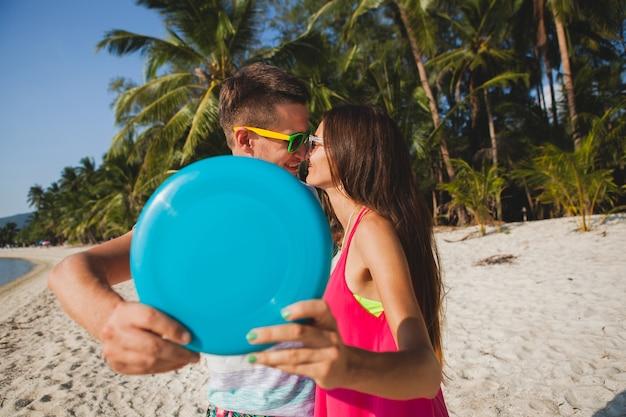 Jong koppel man en vrouw spelen vliegende schijf op tropisch strand, zomervakantie, liefde, romantiek, gelukkige stemming, glimlachen, plezier hebben, hipster outfit, zonnebril, spijkerbroek, zonnig, positieve stemming Gratis Foto