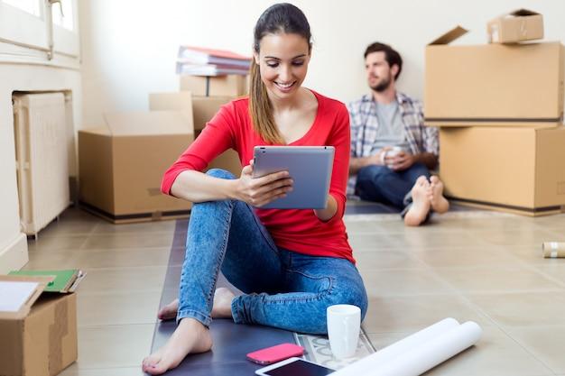 Jong koppel met digitale tablet rusten in hun nieuwe huis Gratis Foto