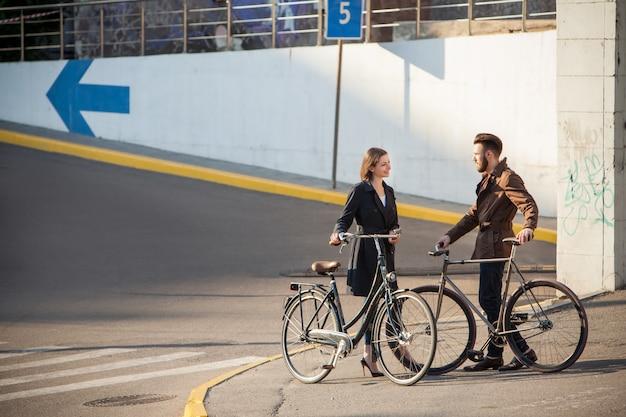 Jong koppel met een fiets tegenover de stad Gratis Foto