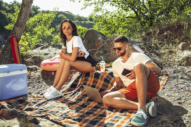 Jong koppel met picknick aan de rivier in zonnige dag. vrouw en man samen tijd besteden aan de natuur. plezier hebben, eten, spelen en lachen. concept van relatie, liefde, zomer, weekend. Gratis Foto