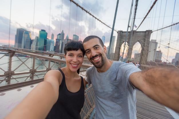 Jong koppel nemen selfie op brooklyn bridge Premium Foto