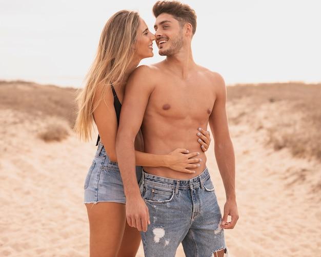 Jong koppel op strand knuffelen Gratis Foto